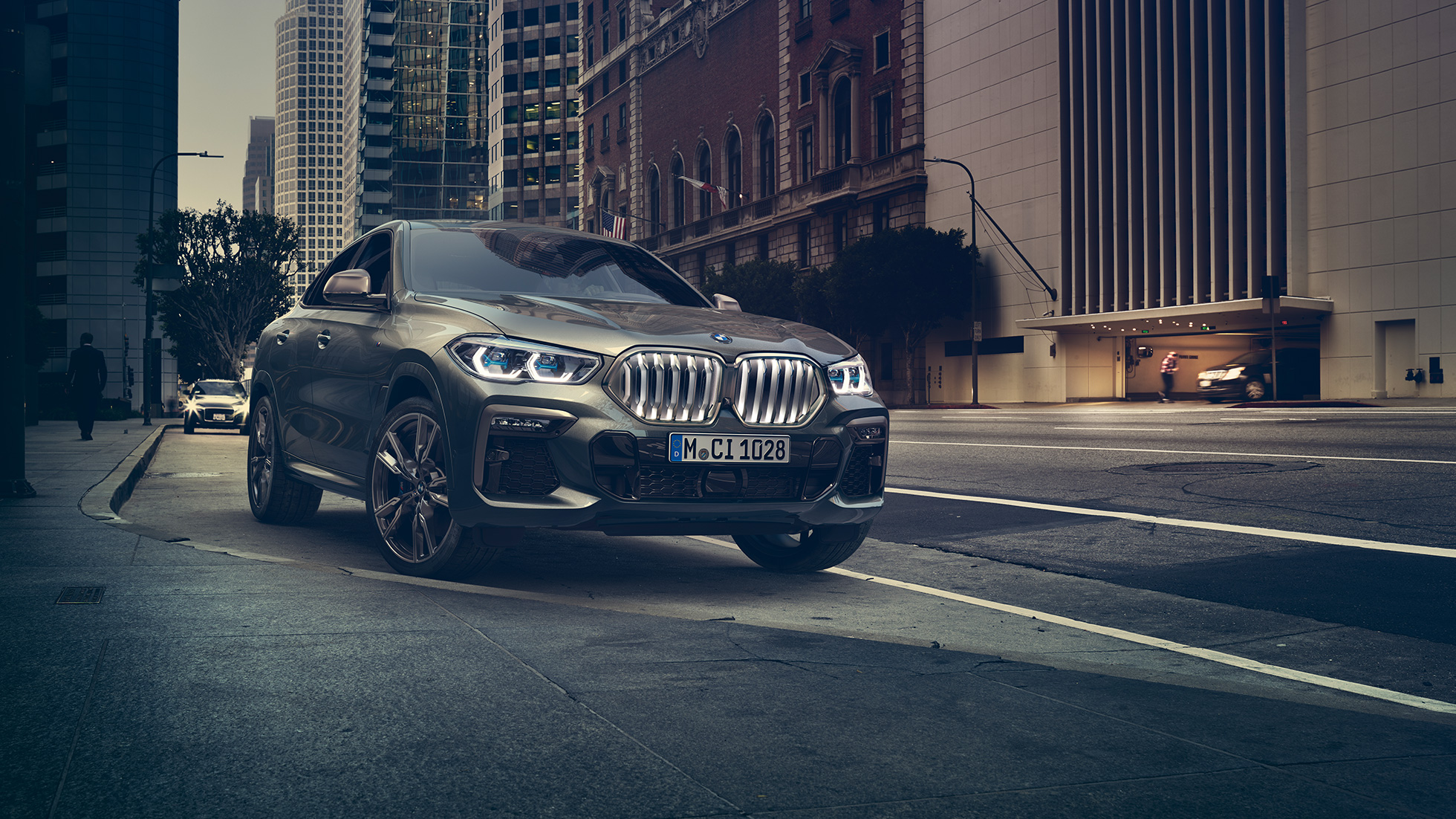 BMW X6 M50i in three-quarter front perspective standing in front of an urban setting